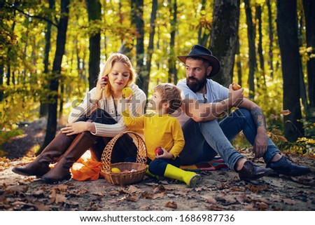 Happy family of three lying in the grass in autumn. A young family with small child having picnic in autumn nature at sunset. Mother, bearded father and kid are eating apples