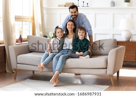 Portrait of smiling bearded father standing near couch with sitting happy wife and little children. Joyful affectionate family of four posing for photo, looking at camera, good relations concept. #1686987931