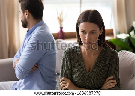 Focus on frustrated frowning young woman sitting separately from upset husband boyfriend on sofa after clarifying relationships at home. Stressed depressed couple ignoring each other after quarrel. #1686987970