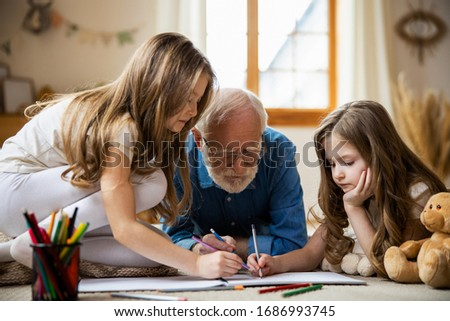 Calm twin girls sitting on the floor and drawing with their grandpa. Domestic concept