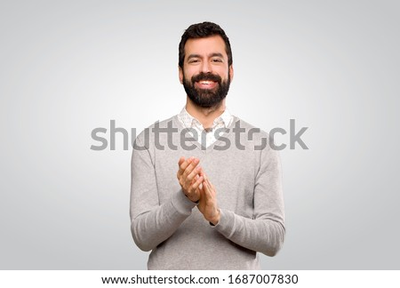 Handsome man applauding after presentation in a conference over isolated grey background Royalty-Free Stock Photo #1687007830