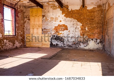 Grungy textured interior of an abandoned and derelict building with flaking walls and exposed  brick and timber beams Royalty-Free Stock Photo #1687034833