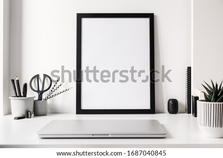 Home office with laptop closed, poster frame mockup and black, grey and white elements. Trendy, creative desk.