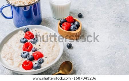Breakfast oatmeal porridge with fresh berries and almond milk. Healthy vegan food concept. Light gray background. Selective focus #1687043236