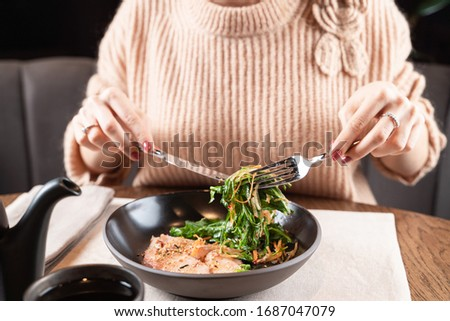 Young woman is having a light snack with fish fillet and lettuce in a seafood restaurant #1687047079