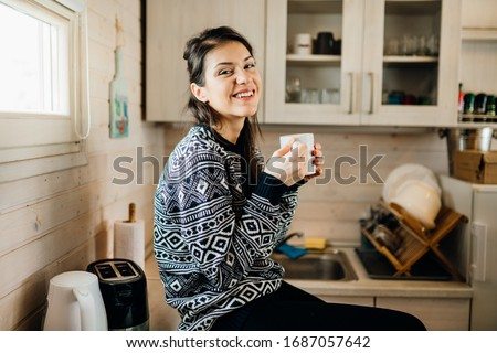 Woman in small kitchen drinking morning coffee.Happiness.Tiny house.First property.Small apartment interior design.Minimalism.Moving in.Living alone.Charming trailer house Royalty-Free Stock Photo #1687057642