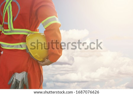 Engineer holding hard helmet with cloud and blue sky background,safety first concept #1687076626