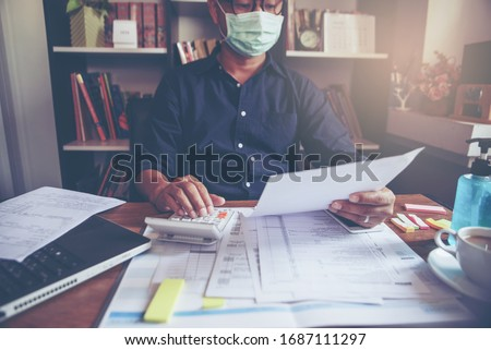 Accountant calculate tax return and work online at home, Asian businessman wear a mask, plan budget and account balance sheet and personal income for worker have income under us law. #1687111297