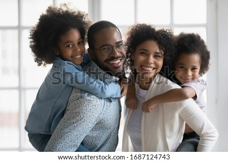 Portrait of African ethnicity parents piggy back son and daughter posing indoors. Pretty family looking at camera photo shoot in modern apartment at home, happy parenthood family services ad concept #1687124743