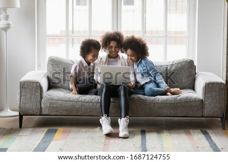 Single African biracial mother and little children sitting on couch using laptop, family enjoy distant talk by videocall, spend time in internet buying, e-commerce users, cartoons or video fun concept