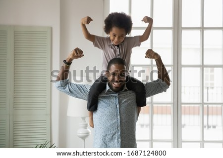 Small son sit on strong dad shoulders showing biceps. African family enjoy activity games at home, healthy fit lifestyle, two superheroes, vitamins for adults and children ad, happy Father Day concept #1687124800