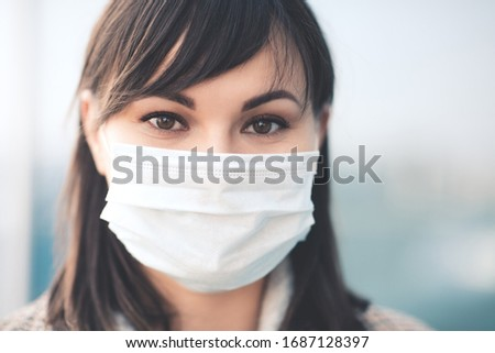 Closeup up portrait of adult woman wearing medical mask outdoors. Looking at camera. Virus concept.  #1687128397