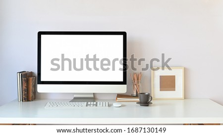 Workspace computer monitor with white blank screen putting on white working desk with wireless keyboard, mouse, coffee cup, picture frame, books and pencil holder over white wall as background.