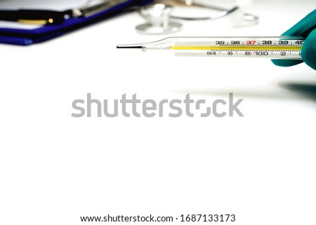 Glass mercury thermometer for known With his hands on her green gloves Located on a white background, near every file, pen, stethoscope The picture at the top right corner has a copy space.