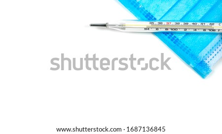 Glass mercury thermometer Placed on a blue mask. The picture on the right. The top corner has a copy space.