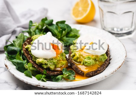 Avocado rye bread toast with poached egg on plate. Healthy appetizer, breakfast, lunch or snack. Runny egg yolk #1687142824