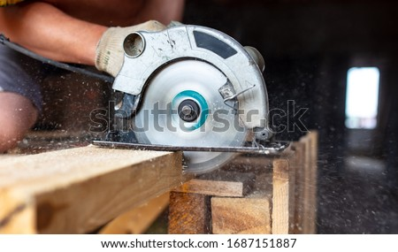 A worker saws a wooden beam. Building a house. #1687151887