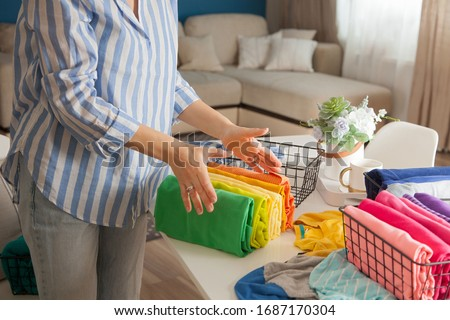Unidentified young woman folds her clothes in a stack of rainbow colors and puts them in a container for an orderly wardrobe. Concept of order and cleanliness in the dressing room #1687170304