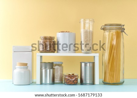 Food staples on pantry shelf prepared to survive Coronavirus COVID 19 pandemic at the time of cuarentine and home isolation. Groceries on colorful background