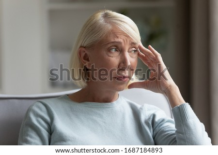 Upset senior woman sit on couch at home look in distance mourning, sad distressed mature female lost in thoughts, miss old days, thinking or pondering, feeling lonely, elderly solitude concept #1687184893
