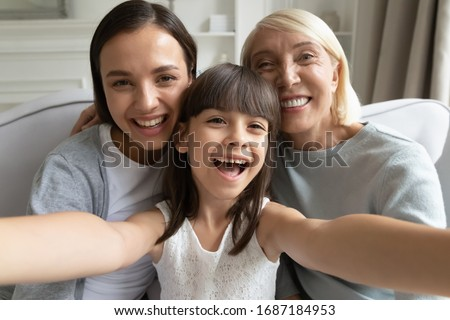Close up portrait of overjoyed three generations of women have fun at home make selfie together, smiling little girl with young mom and senior grandmother take self-portrait picture on camera