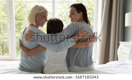 Back view of happy three generations of women sit on bed hugging hope for bright future together, smiling little girl with young mother and senior granny embrace at home show unity and support #1687185043