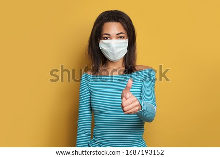 Black African American woman in face mask showing thumb up on yellow background #1687193152