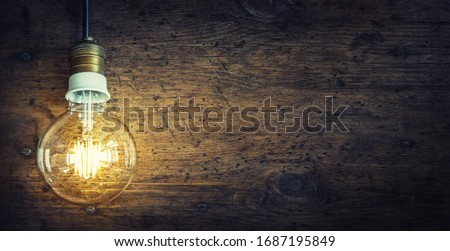Luminous old lamp on an retro wood surface with copy space. #1687195849