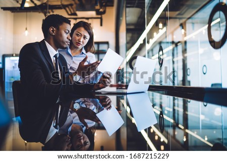 Successful African American businessman sharing opinion with listening carefully Asian female colleague while sitting at counter with laptop and pointing at paper document #1687215229