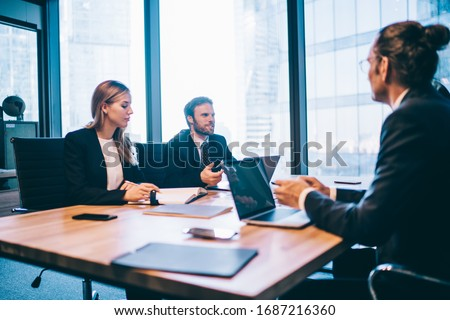 Confident male and female partners have financial brainstorming during work day in modern workspace with internet connection for laptops, group of successful employees discussing corporate strategy Royalty-Free Stock Photo #1687216360