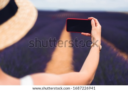 Back view of crop unrecognizable female in hat holding phone with empty screen and taking picture while standing during holidays on lavender fields in Provence in France