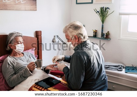 Sick elderly woman of COVID-19 lies in bed at home wearing medical mask. Her husband takes care of her. Two senior people at home. Quarantine self-isolation concept Royalty-Free Stock Photo #1687230346