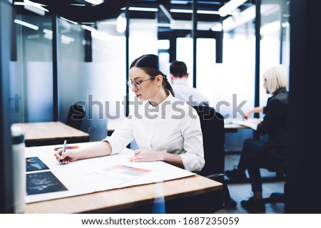 View through glass wall of concentrated businesswoman sitting at table drawing draft with blurred blurred colleagues on background working in modern office #1687235059