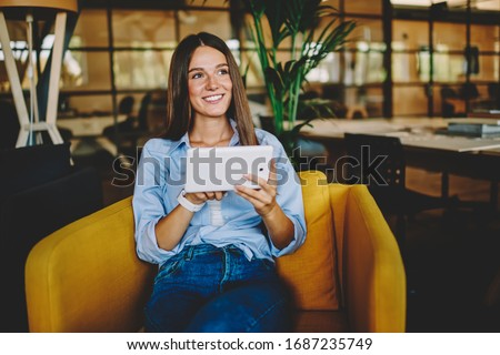 Cheerful Caucasian woman dressed in casual apparel looking away while updating touch pad, carefree female blogger using digital tablet for communicate with followers connecting to 4g wireless #1687235749