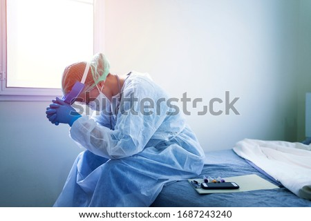 doctor in PPE suit uniform has stress in Coronavirus outbreak or Covid-19, Concept of Covid-19 quarantine.Emotional stress of overworked doctor and medical care team during covid-10 period.  Royalty-Free Stock Photo #1687243240