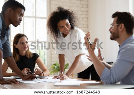 Team leader talk at briefing express point of view to diverse teammates, multiracial young workers brainstorming in board room discuss new project, process of negotiations at business meeting concept Royalty-Free Stock Photo #1687244548