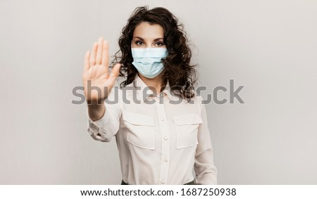 Masked woman makes stopping hand gesture. Influencer Girl blogger in medical mask talks about covid-19, coronavirus. Girl in medical mask stops 2019-nCov Royalty-Free Stock Photo #1687250938