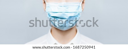 Girl Doctor wearing protection face mask against covid-19. Banner panorama medical staff preventive gear about coronavirus. Woman in medical mask stops 2019-nCov #1687250941