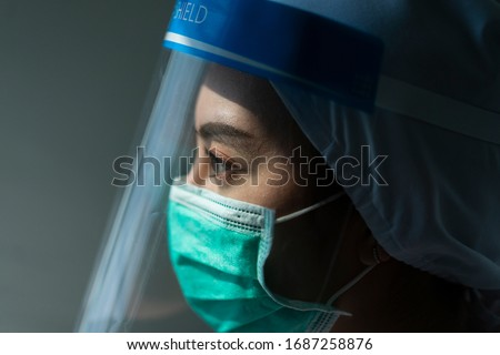 Closeup Asian female Doctor wearing face shield and PPE suit for Coronavirus outbreak or Covid-19, Concept of Covid-19 quarantine Royalty-Free Stock Photo #1687258876