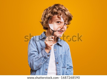 Positive curious schoolboy in casual wear looking at camera through magnifier while standing against bright orange background Royalty-Free Stock Photo #1687268590