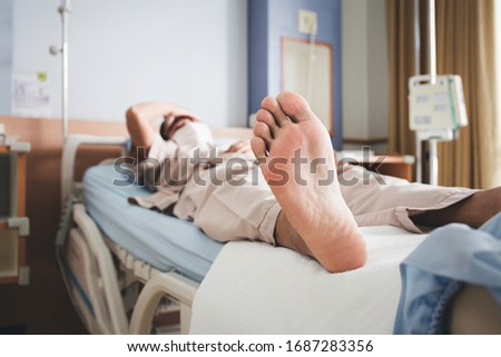 Focus on the feet of patients lying on the hospital bed #1687283356