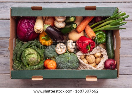 Fresh organic vegetable delivery box on a wooden background Royalty-Free Stock Photo #1687307662