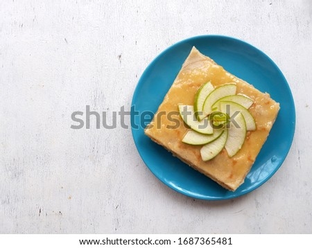 Rose decoration from apples on an apple-honey pancakes. White table. Picture from up front. Closeup pancake pastry on a blue plate.