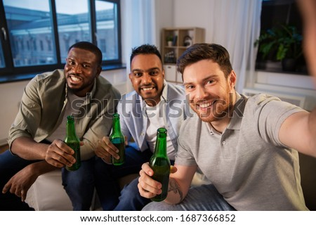 friendship, leisure and people concept - happy smiling male friends taking selfie and drinking beer at home