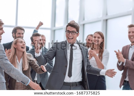 happy young businessman standing in front of his business team. #1687375825