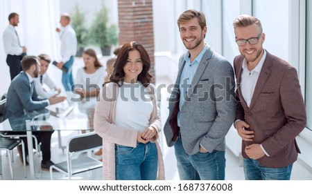 three young employees standing in a modern office. #1687376008