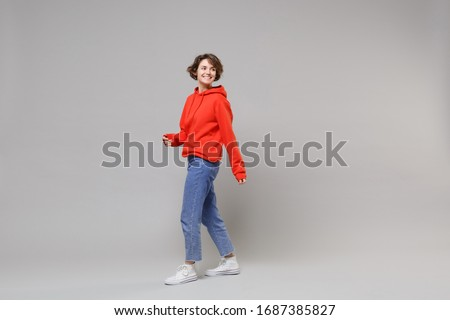 Side view of pretty young brunette woman girl in casual red hoodie, blue jeans posing isolated on grey wall background studio portrait. People lifestyle concept. Mock up copy space. Looking aside Royalty-Free Stock Photo #1687385827