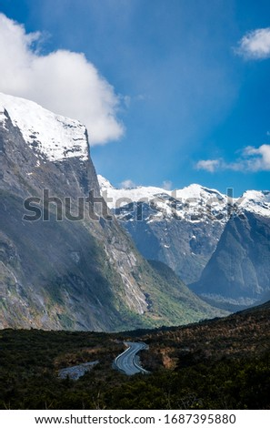 Stunning image of the SH94 road towards Milford Sound with the snow capped mountains in the background taken on a sunny winter day, New Zealand #1687395880