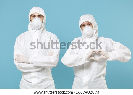 People in protective suits respirator masks isolated on blue background studio. Epidemic new rapidly spreading coronavirus 2019-ncov originating in Wuhan China virus concept showing shape heart hand #1687402093