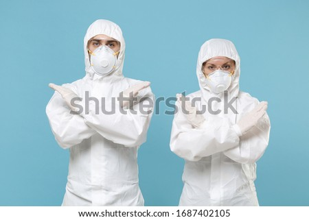 Two people in protective suits respirator masks isolated on blue background studio. Epidemic pandemic new rapidly spreading coronavirus 2019-ncov originating in Wuhan China medicine flu virus concept #1687402105